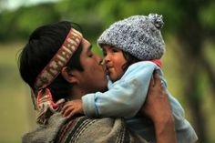 Chile - A Mapuche native kisses his son in the village of Temucuicui in Temuco, Nov. 13, 2009. (Martin Bernetti/AFP/Getty Images)