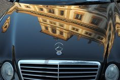 Palace on the car - Precise design of a historic building on a modern Mercedes in front of Tuscany palace in Prague
