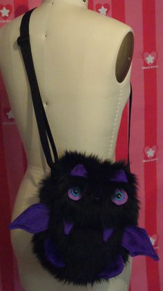 Adorable fuzzy bag purse/messenger style bag. Carry all your items inside your furry friend. Original design made from hand drawn paper pattern pieces. Details: Soft luxurious black faux fur Purple minky fabric details; Wings, feet, fangs, ear insides. Blue acrylic plastic eyes, black plastic nose Velcro closure One (1) long adjustable black strap with plastic slider. This is NOT a backpack. Fully lined with cotton denim. Large inside pocket, holds phone, keys, wallet, make up and more! 10…