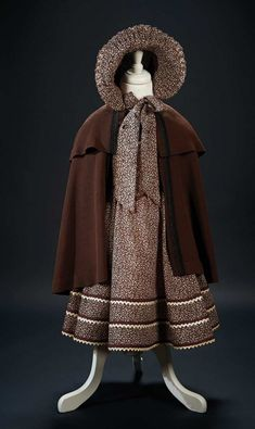 """Love, Shirley Temple, Collector's Book: 231 Brown Print Dress with Bonnet and Brown Cape Worn by Shirley Temple in the Film """"Dimples"""""""