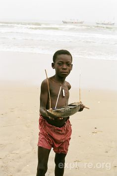 Boy with a wooden boat in Cape Coast, Ghana.