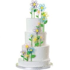 Ribbon-like quilling flowers give this elegantly tiered cake a contemporary lift. For the stems, paint Lollipop Sticks with green-tinted vanilla extract and add fondant leaves created with a Rose Leaf Fondant Cut & Press Set.