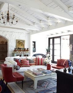 White wood plank ceiling, stunning chandelier, dark French doors, white sofa, red chairs, Southwestern navajo rug and patriotic pillows. What's not to love?! Malcolm McDowell's Ojai home. House Beautiful