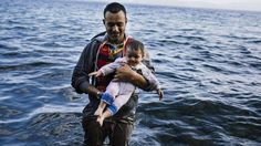 A man carries his child shortly after he arrived, with other refugees and migrants, on the Greek island of Lesbos, after crossing the Aegean sea from Turkey, on 12 October 2015