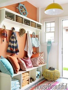 Entry way? Love the concept of storage boxes for everyone's crap.  Nix the awkward throw pillows and the orange.
