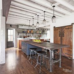 Exposed ceiling beams heighten the kitchen's loftlike vibe. This kitchen design gives the feel of a restaurant, the island allows you to prep, serve, and eat all at the same space.