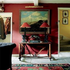 Red Sanderson walls are offset by pale stone flooring. An antique console table with red lamps, a bronze and two urns makes a symmetrical display beneath an old painting | Homes & Gardens |