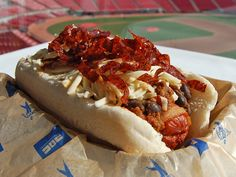 Cincinnati Reds: Meat Lovers Dog. Could this be the ultimate meat-on-meat hot dog? This over-the-top locally sourced meat atrocity consists of a quarter-pound hot dog from Cincys own Queen City Sausage, wrapped in bacon, deep-fried and topped with beef and black bean chili, shredded jack cheese, and garnished with ribbons of crispy fried salami. All piled into a hoagie bun from nearby Klosterman Baking Co.