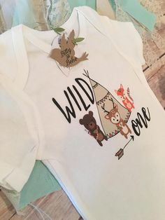 WILD ONE! This bodysuit (or T-Shirt) is so adorable and is perfect to use as at a party for the First Birthday Boy, at a Baby Shower with a Woodland Theme or Everyday Wear. This Cute Baby Bodysuit (or T-Shirt) is so cute for the Boho baby boy (or girl) with Teepee with flag pennant banner details, a tribal style bear with arrows, fox and deer with feathers, also features an arrow and WILD ONE printed across the front. Fun Hipster/Bohemian Festival style. Perfect for your little man or b...