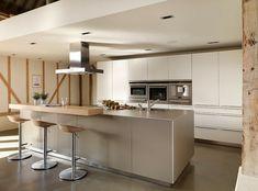 un îlot gris clair et des armoires blanches aux accents métalliques dans la cuisine