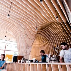 Zmianatematu by xm3  -- plywood forms undulate down in cave-like fashion in this coffee shop in Lodz, Poland.