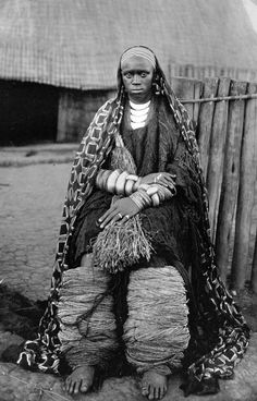 Africa | Well off local woman sitting in front of a cottage. 1928 | ©Major R. Høier / National Museum of Denmark || Given other photos within the collection, possibly taken in Rwanda