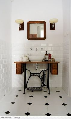Great use of a sewing machine base as a sink base.  The black wrought iron treadle fits in so well with the black, white and dark brown color scheme