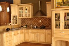 I like the natural maple kitchen cabinets with dark inset in moulding. cool!