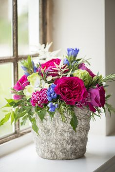 """Our magenta-pink Kate garden roses radiate against the cool blue and green hues in this antique stone vase. This quintessential #floralarrangement could be the """"center of the table"""" star at your #outdoorwedding reception!"""