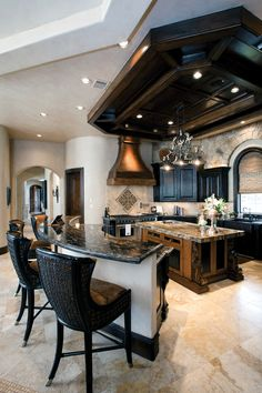 Now THAT is a kitchen! The black cabinets and ceiling, the copper above the stove, the marble and the stone....everything I love!!!
