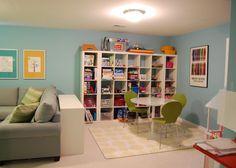 salle de jeu dans un coin du salon en sous-sol avec étagère de rangement…