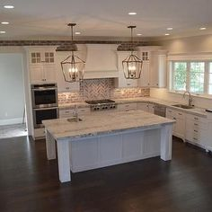 Classic Charleston Style Farmhouse Kitchen with brick backsplash, painted island and lantern pendant lights