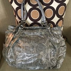 "B. MAKOWSKY OH SO SASSY PURSE! Get this textured material purse with metallic black, silver, and taupe coloring.  It has the cute tag with the brand name on the front, as well as the silver color plate with the name.  Beautiful purse with lots of room inside.  Contrasting beautiful printed material inside.  A pocket on either side of the purse for extra storage.  17"" across at widest, 11"" long, straps extend 11"". Clean inside and out.  Handles have turned slightly darker gray based on normal…"