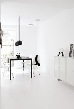 black and white scandinavian home decor. Black dining table, white cabinets, white eames chairs, white walls, black light pendants...