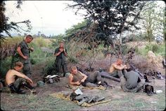 """""""CAPT Tucker standing on left with c-ration can in his left hand. He is listening to SGT Temple who has radio handset in his hand relaying message from Battalion HQ. Photo taken in spring 1967 and provided by SGT Mike Kovitch, RTO Alpha 2-7 Cav."""""""
