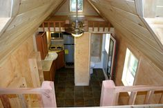 "Tiny house interior; this one looks like one of the plans from Tumbleweed - it's distinctive, with two lofts on either end of the ""great room"". I like the tile floor; only a two-burner hot plate in the kitchen, though.  tiny-house-with-studio-3"