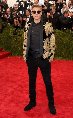 """Justin Bieber arrived to the 2015 Met Gala in a custom Balmain black coat with golden dragon detail, styled by Ugo Mozie, which made him one of the few men on the carpet who really went for it with the theme this year, which is """"China: Through the Looking Glass.""""  Justin Bieber, Met Gala 2015"""