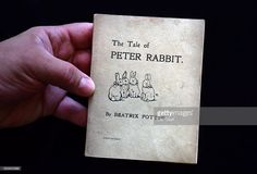 An assistant holds a first edition of The Tale of Peter Rabbit by Beatrix Potter at Dreweatts and Bloomsbury Auctions on July 27, 2016 in London, England. Forming part of a Beatrix Potter Books and Works on Paper sale on 28th July 2016, it is one of 60 lots and is expected to fetch between 25,000-35,000GBP.