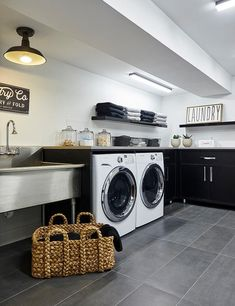 Black basement laundry room displays white front load washer and dryer enclosed by black cabinets topped with gray countertops next to a freestanding stainless steel laundry room sink.