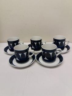 Raija Uosikkisen suunnitteleman Sotka -sarjan kahvikupit, 5 kpl. Kupit ja lautaset ovat ehjiä ja siistikuntoisia, pieniä käytön jälkiä pinnoissa näkyy, samoin muutama valmistuksessa tullut piste ja värijälki. Kupin korkeus 6,8 cm, halkaisija 6 cm, lautaset halkaisija 12 cm. Käsinmaalattu. MYYTY. Tableware, Runway, Dinnerware, Tablewares, Dishes, Place Settings