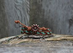 This beaded double wrap bracelet features picasso seed beads in red and seafoam green turquoise. They were handwoven between 2 rows of light brown leather. Fastens easily with a handmade copper daisy button.    So easy to wear, simply wrap around your wrist 2 times and fasten the button for a great casual look. Looks awesome with your favorite t-shirts, jeans and boots!     This wrap offers a two loop fitting. It measures 14 inches and 15 inches. Please measure your wrist carefully.    All…