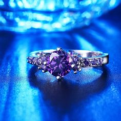 Purple zirconia ring featuring a round centre gem set in the company of a number of smaller ones.  Beautiful and unusual, it's the perfect jewel for many occasions! Whether it's a birthday, engagement or Christmas gift, any lady would be happy to have it!  Thanks to the highly polished s