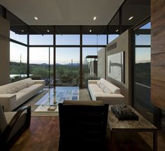 white ceiling transitions to darker wood soffit outside.    modern living room by the construction zone, ltd.
