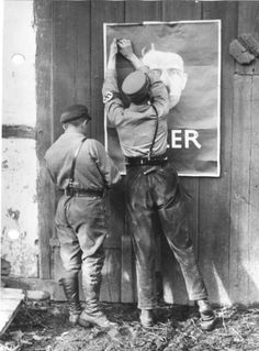Two German Nazi Party SA men putting up an election poster featuring Adolf Hitler, Mecklenburg, Germany, summer 1932