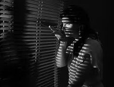this film noir photo uses side lighting and uses blinds to separate the light to create black lines of shadows on the girls face and frontal lighting on the man to cast the silhouette on the wall