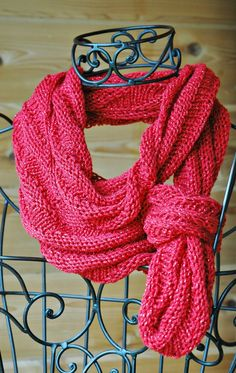 Feel powerful in this hand knit red metallic yarn infinity scarf. There are lots of ways to wear this long, (72 inch diameter) wide, (7 inches) soft bit of bling in a scarf. You can loop it around your neck 3 times for a cozy cowl effect. Two loops gives you a long scarf. Tie a knot in it and show some style. Reds are difficult to photograph and monitors see things differently. This scarf is a deep tomato or lipstick red with a silver thread running through it.ISC0002