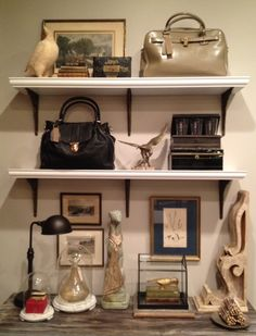 display with handbags, greyhound statue, and various antique pieces