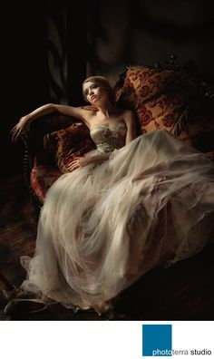 Phototerra Studio - Renaissance Bride: I created the image of this bride laying on a love seat with beautiful light, during a wedding in St. Petersburg, Russia.I shot this moment with one light through a grid to create an amazing feeling of daylight shining through a window. The bride's relaxed pose for this photograph was inspired by renaissance paintings, with her beautiful dress flowing down the love seat she is sitting on. This image beautifully demonstrates how emotionally evocative…