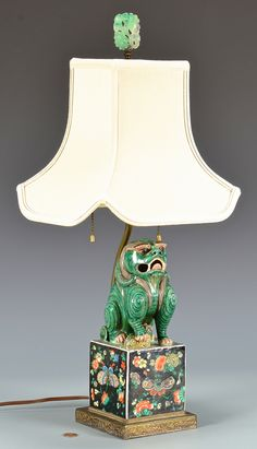 Chinese polychrome porcelain foo dog, mounted as a lamp, standing with raised paw on smaller foo dog, mounted on square Famille Rose porcelain plinth with chased brass base. Double socket with gree…