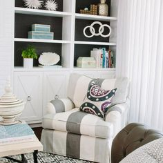 Chic living room features an ivory and gray striped armchair adorned with a black and purple suzani pillow atop a black and gray geometric rug placed in front of a wall of built ins, with backs of shelves clad in black grasscloth, stacked atop cabinets with x overlay trim.