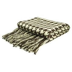 """Cashmere and wool throw with a chocolate and creme houndstooth motif.  Product: ThrowConstruction Material: Cashmere-wool blendColor: Chocolate and cremeFeatures: Six inch fringeDimensions: 50"""" x 65""""Cleaning and Care: Dry clean"""