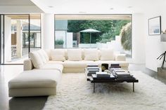 Gemütlichkeit pur im Wohnbereich. Die weiße Polsterlandschaft, ein langfloriger Teppich sowie ein Panoramafenster, das den Ausblick in den Garten quasi einrahmt. Foto: Vipp // Mehr auf livvi.de