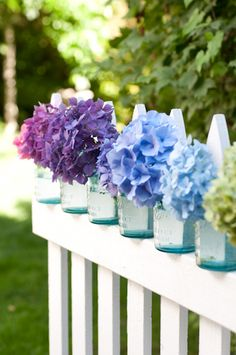 Multi-colored Hydrangea macrophylla blooms in vintage canning jars on picket fence by Georgianna Lane