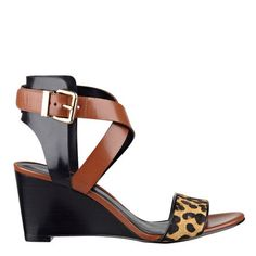 "Meow! We think you'll love our Nofrills streamlined crisscross strap wedge heels. These open toe sandals feature a chic wedge heel and a sleek leopard print band across the vamp. Adjustable buckle closure. Padded footbed for all-day comfort. Leather upper. Man-made lining and sole. Imported. 2 3/4"" mid heels."