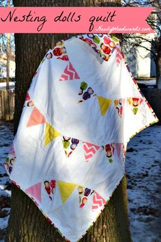Make a whimsical nesting dolls pennant quilt for a baby girl.