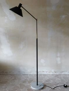 This vintage Italian floor lamp was produced by Stilux in the 1950s. The height is adjustable. It features a brass structure, marble base and black metal swiveling shade.