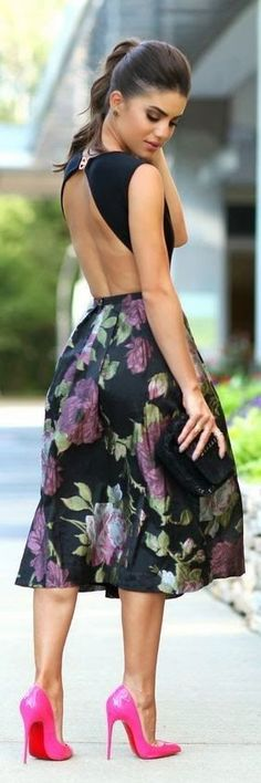Dress with open back with floral pattern, black clutch and ponytail hairstyle.