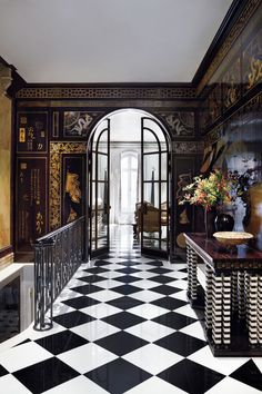 In Molyneux's Upper East Side townhouse, lacquered wood paneling and marble floors line the second-floor foyer. The bone-and-ebony table, topped with sturgeon skin, is his own design.