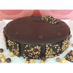 """Noutellino Cake in Cyprus - This incredible creation starts with a bottom layer of our moist chocolate sponge, topped with our """"melt in your mouth"""" chocolate mousse, nutella, meringue, chopped hazelnuts and then covered with chocolate glaze and hazelnuts."""