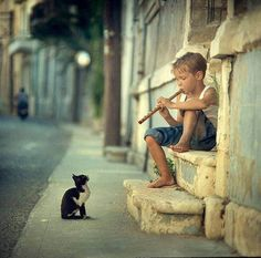 Little boy playing the flute, with an attentive cat.